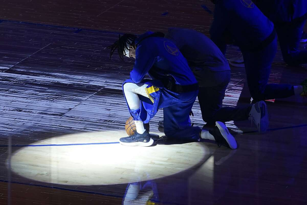 Warriors guard Damion Lee and teammates kneel during the national anthem a game against the Clippers on Wednesday.