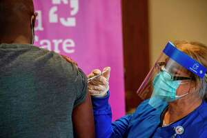 Nurse Keith Grant is given the second dose of the Pfizer/BioNTech vaccine twenty-one days after receiving the first shot from RN Valerie Massaro of Hartford HealthCare at the Hartford Convention Center in Hartford, Connecticut on January 4, 2021.