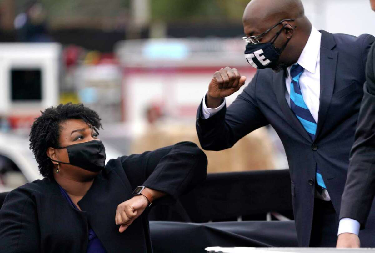 U.S. Democratic Sen.-elect Raphael Warnock, right, bumps elbows with Stacey Abrams during a campaign rally with U.S. President-elect Joe Biden in Atlanta last month.
