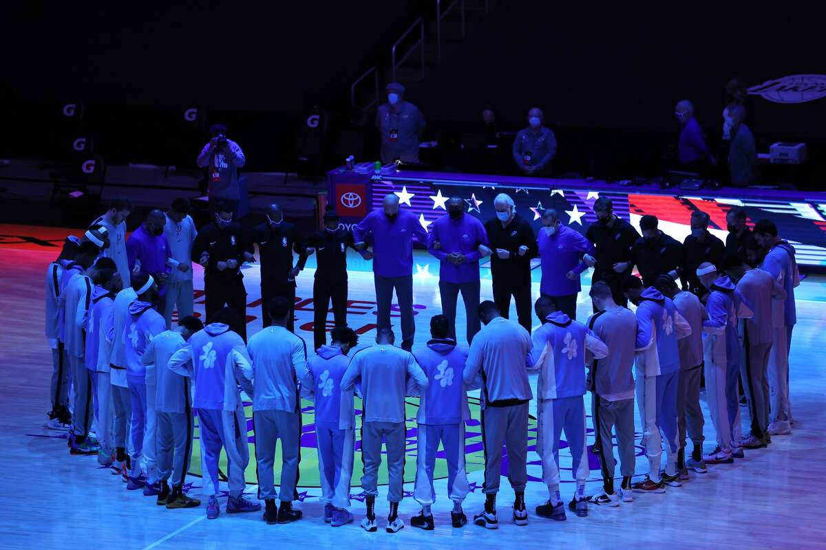 LOS ANGELES, CALIFORNIA - JANUARY 07: The Los Angeles Lakers and the San Antonio Spurs lock arms during the national anthem prior to a game at Staples Center on January 07, 2021 in Los Angeles, California. (Photo by Sean M. Haffey/Getty Images)