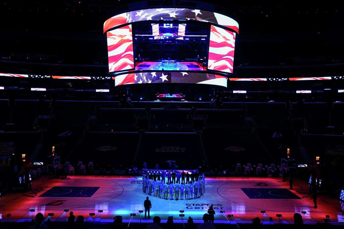 The San Antonio Spurs and the Los Angeles Lakers stand in a circle as the national anthem is played before an NBA basketball game Thursday, Jan. 7, 2021, in Los Angeles. (AP Photo/Ashley Landis)