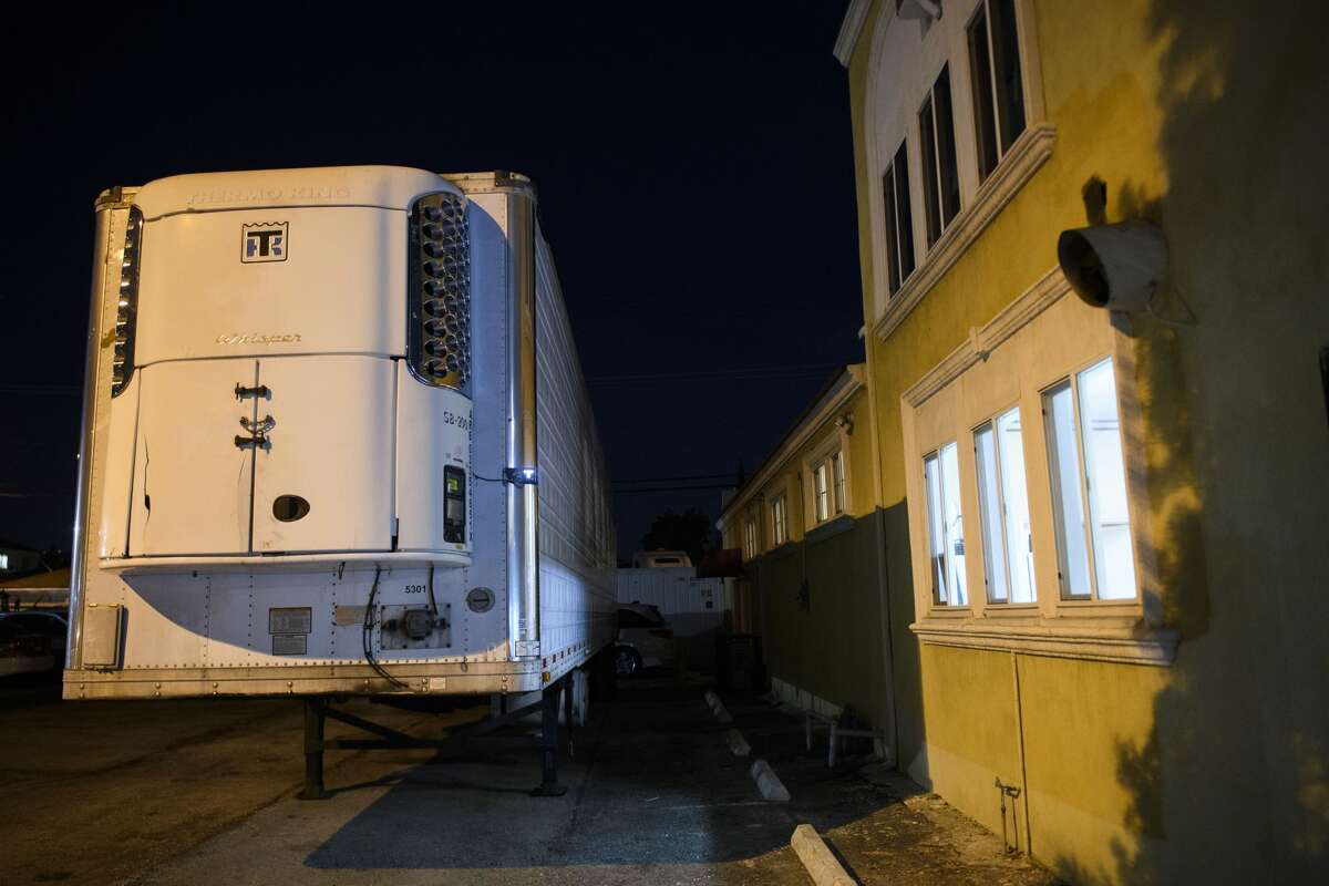 A refrigerated semitrailer stands parked outside of Continental Funeral Home, required to accommodate an influx of people who have died due to COVID-19, on Dec. 30, 2020, in East Los Angeles, California.