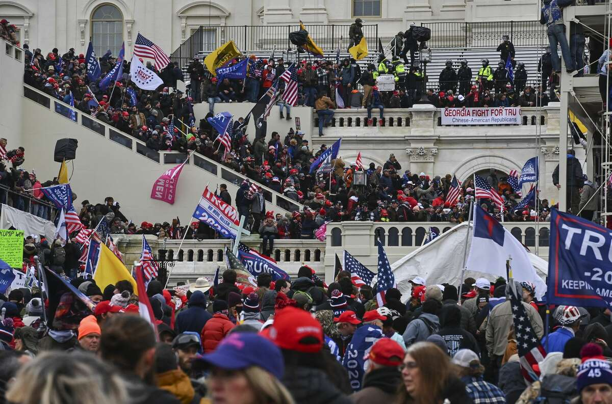 Protesters take over the Inaugural stage during a protest calling for legislators to overturn the election results in President Donald Trump's favor at the U.S. Capitol on January 6, 2021 in Washington, D.C. (Photo by Ricky Carioti/The Washington Post via Getty Images)