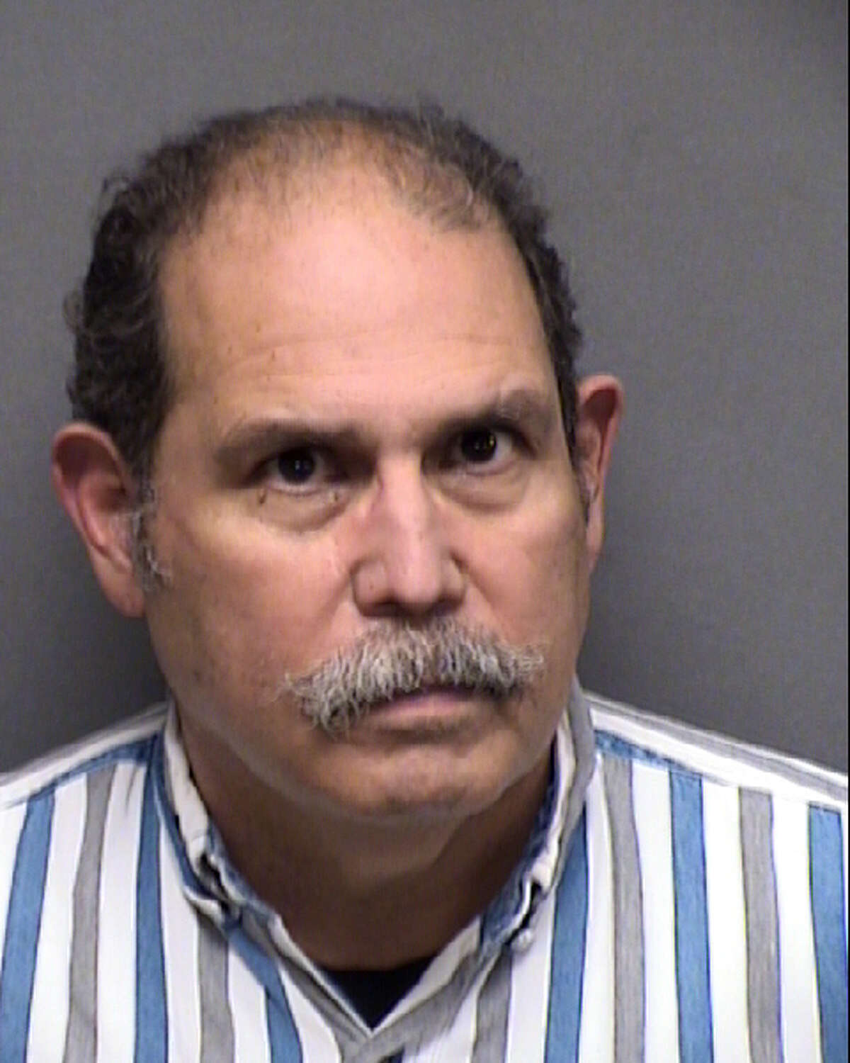 Former Bexar County deputy Danilo Molina, 68, was charged with tampering with government records after allegedly having inmates perform his cell checks, but putting in his logs that he was conducting them.