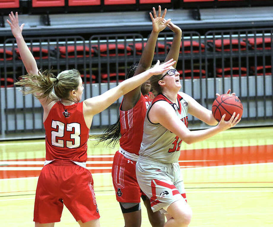 SIUE's Madison Webb (right) splits a pair of Austin Peay defenders to get off a reverse layup that would not fall during the first half Thursday afternoon at First Community Arena in Edwardsville. The Cougars are back home at the FCA to play Murray State on Saturday. Photo: Greg Shashack / The Telegraph