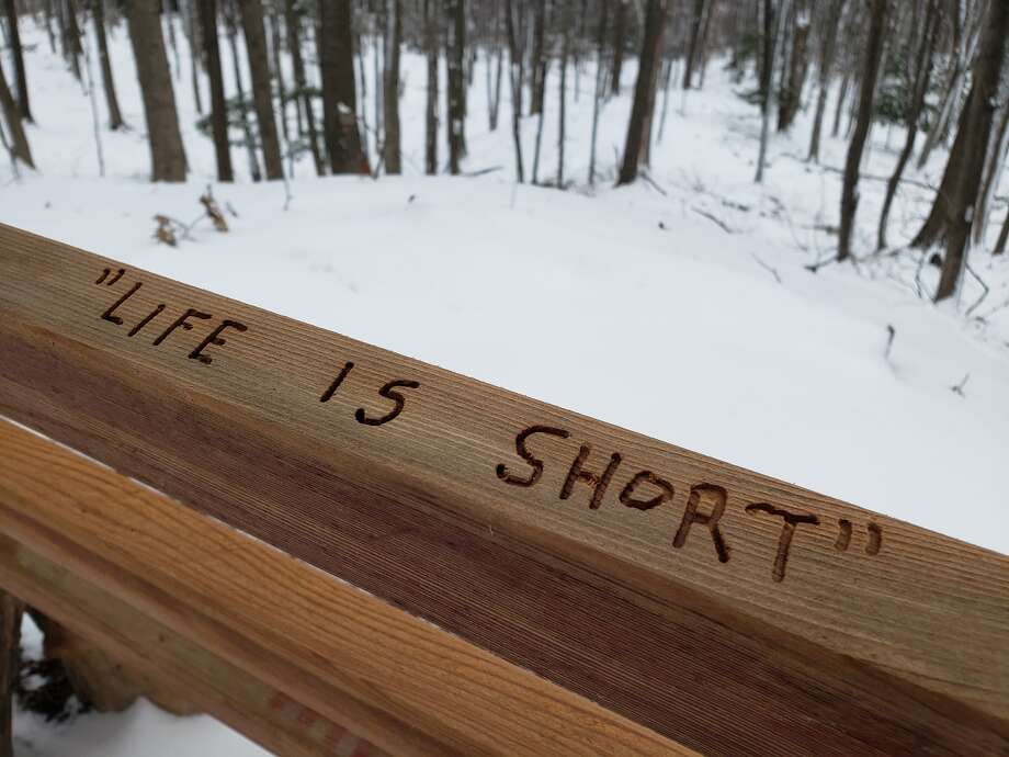 """Arielle Breen's first #52HikeChallenge of 2021 was at the Jack Fern Trail in Manistee. Along that trail is a bench with the phrases """"Life is short"""" and """"'Sit a spell' enjoy the view"""" engraved on the top. Photo: Arielle Breen/News Advocate"""