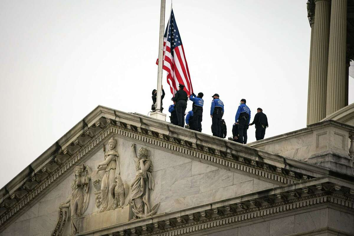 Members of the U.S. Capitol Police bike team lower the American flag at the U.S. Capitol in Washington, D.C., U.S., on Friday, Jan. 8, 2021. House Speaker Pelosi orderedflagsat the Capitol to fly at half-staff after the death of Capitol Police Officer Brian Sicknick, who was fatally injured during Wednesday's violence. Photographer: Al Drago/Bloomberg