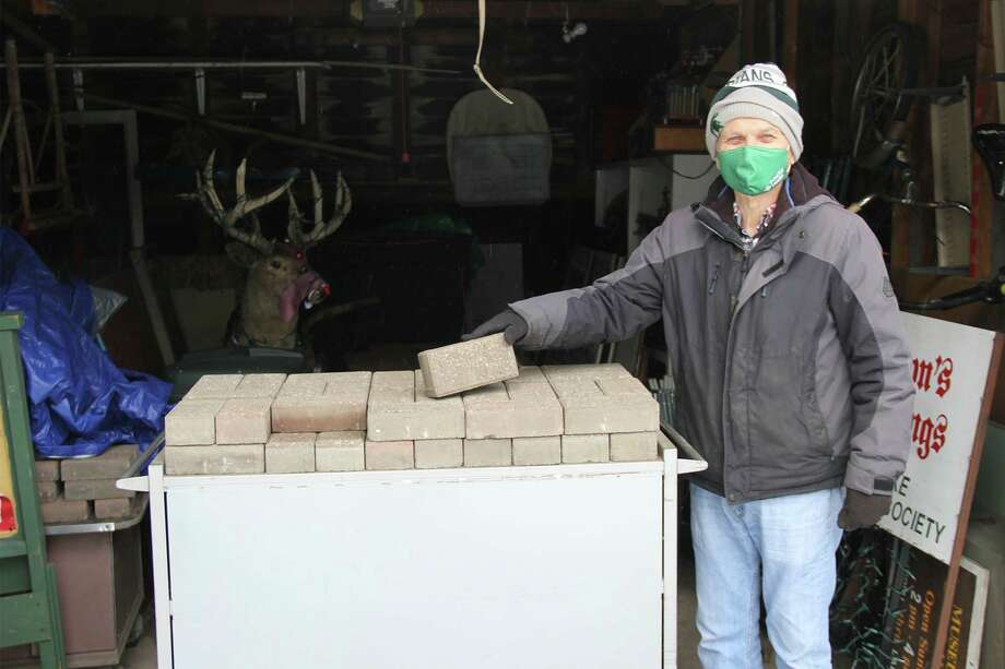 Bob Johsnon, a member of the Bad Axe Historical Society, shows off the bricks they have to sale. The bricks will be engraved with the names of the donors and lain in the sidewalk leading to the society's Allen House's front door. (Robert Creenan/Huron Daily Tribune)