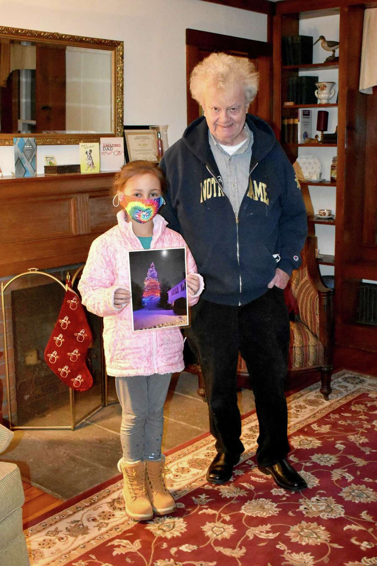 Patrick Shelley of Winchester and his neighbor's granddaughter, Molly, who lights the tree every year.