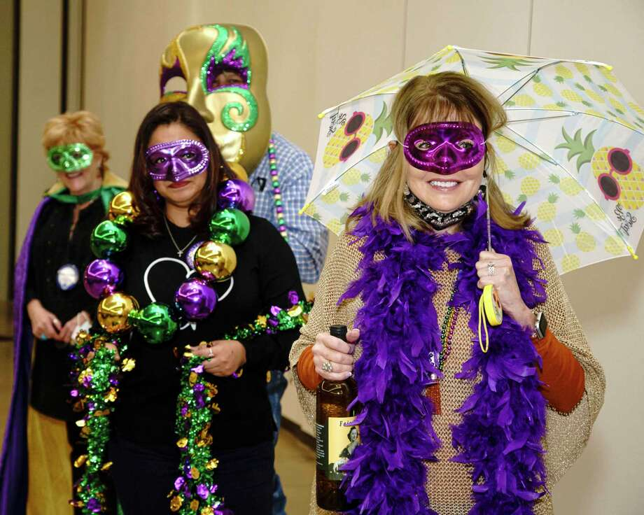 Members of the Conroe Noon Lions Club are preparing for their annual Dinner/Dance & Auction coming up on Feb. 11 and they kicked off announcements with a 'second line' at the club meeting Wednesday. Pictured front to back are Karen Lonon, Lorena Garcia, Scott Perry, Sara Coots. Photo: Courtesy Photo / constance mcnabb dvm