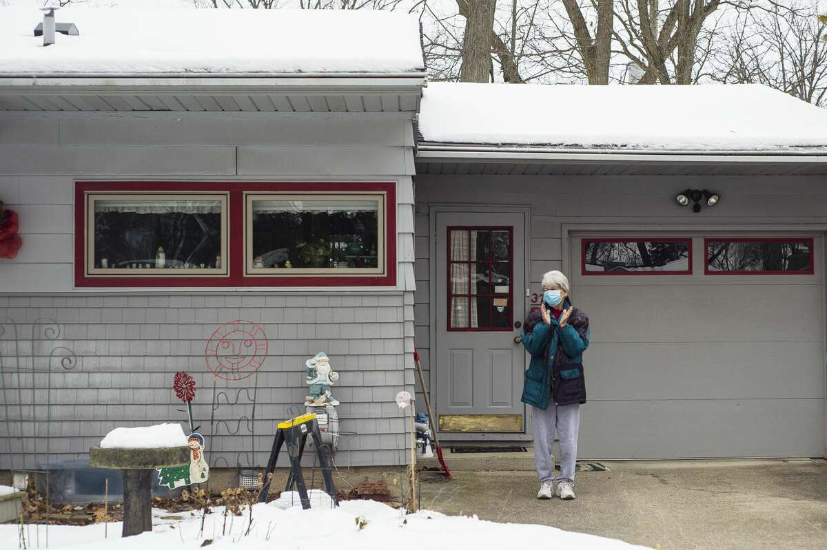 Connie Lesh emerges from her home as a group of her friends and fellow Chemical City Garden Club members congregate outside of Lesh's home Friday, Jan. 8, 2021 to wish her a happy 79th birthday. (Katy Kildee/kkildee@mdn.net)