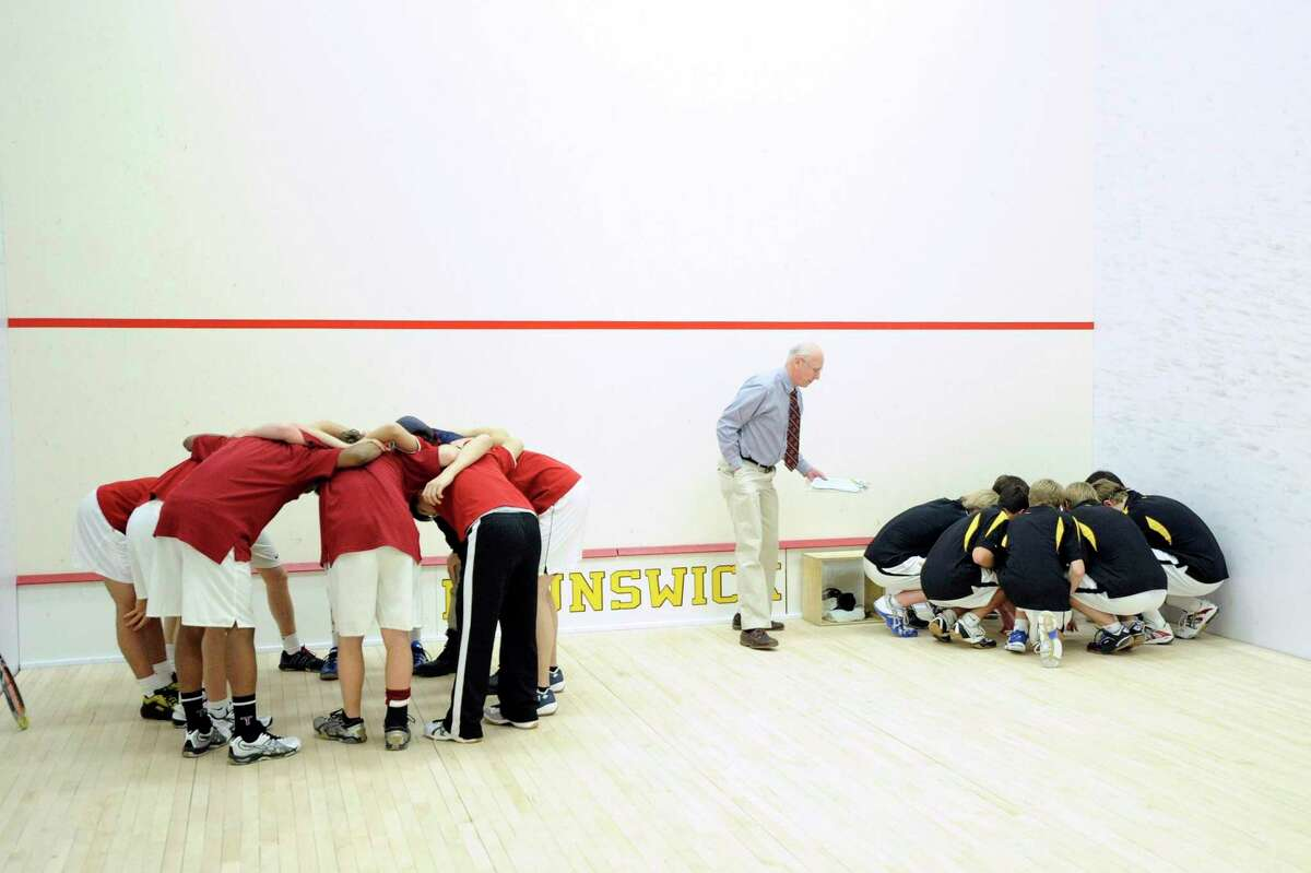 The Taft School squash team, left, and the Brunswick School squash team, right, huddle prior to squash match between Brunswick School and Taft School, at Brunswick School, Greenwich, Saturday afternoon, Jan. 29, 2011. In the center of photo is Brunswick School squash coach Jim Stephens.