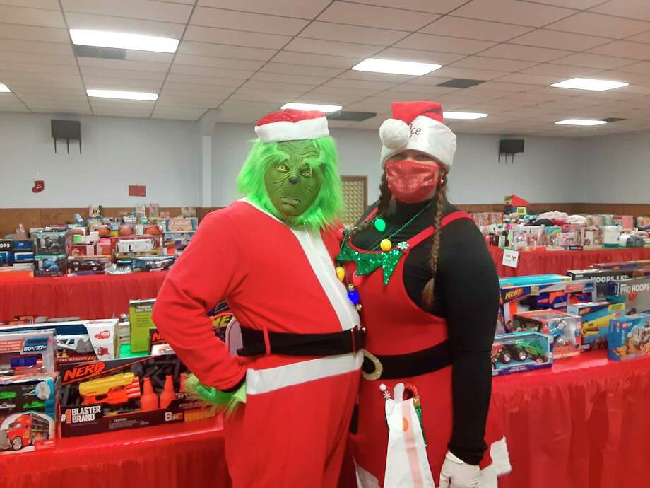 FiveCAP volunteers helped make theToys for Tots/Gifts for Teens programasuccess in 2020. Justin and Amber Sedelmaier dressed as the Grinch and an elf, respectively. (Courtesy photo)