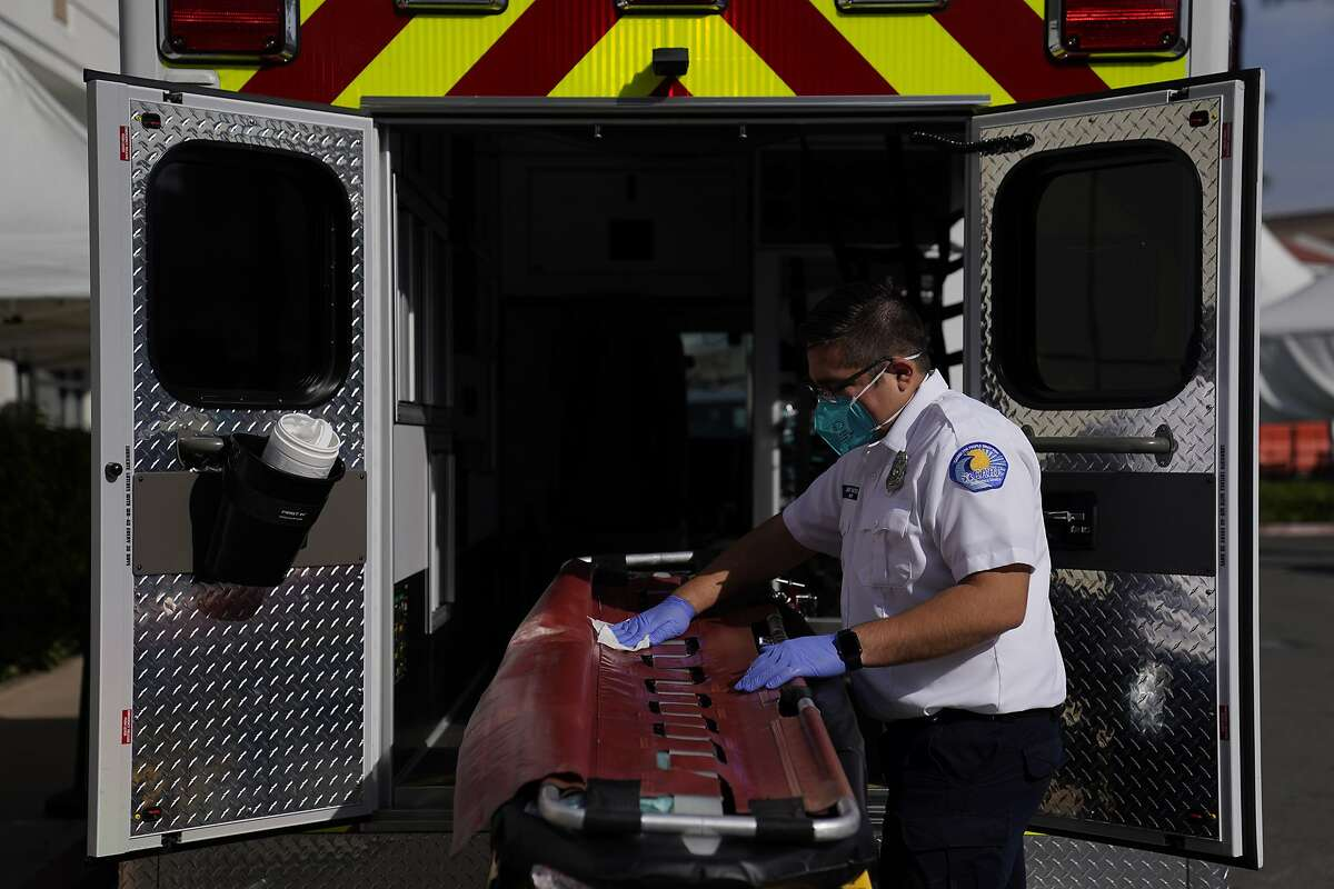 An emergency medical technician disinfects a gurney after transporting a patient in Orange County.