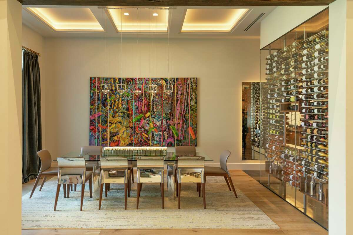 The dining room has a triple coffered ceiling with cove lighting, and a chandelier with slender cables that won't disrupt the view of artwork by New Zealand painter Jimmy James Kouratoras.