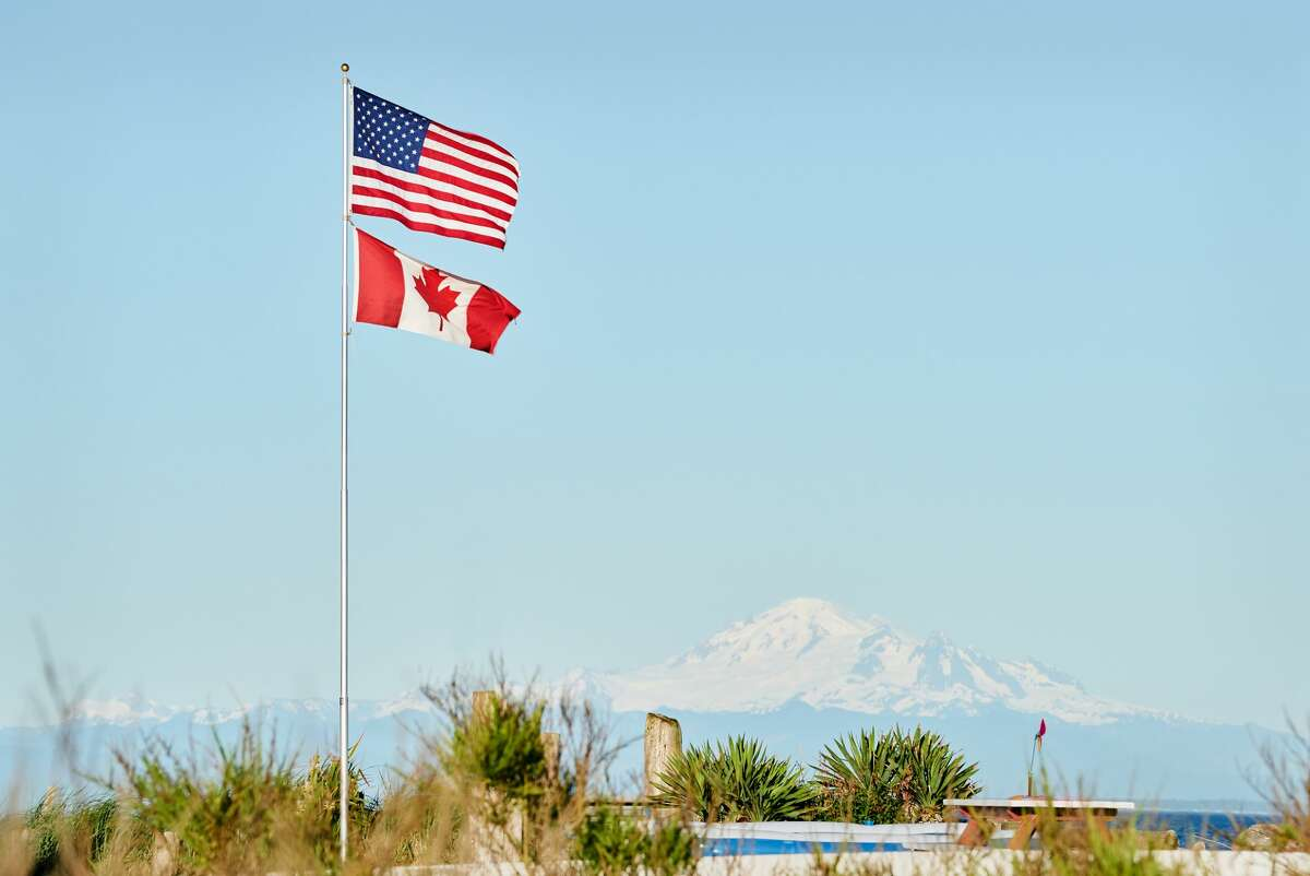 US and Canadian Flags fly in Point Roberts, Washington State.
