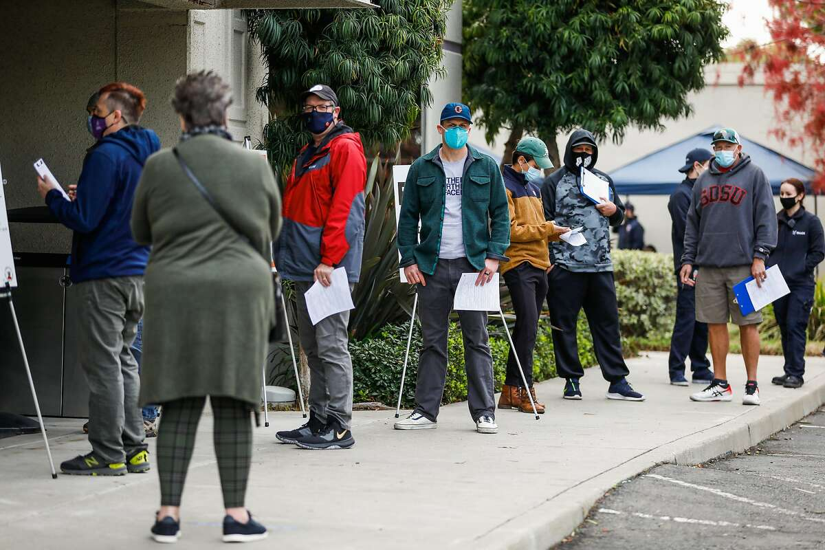 People wait outside of St. Rose Hospital to get either their first or second dosage of the COVID-19 vaccine on Wednesday, Jan. 6, 2021 in Hayward, California.
