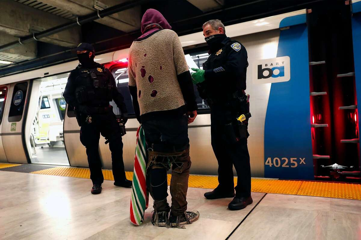BART police Officers Eric Hofstein (right) and Nathan Young talk with a man in Civic Center Station after they say he threw drugs onto the tracks.