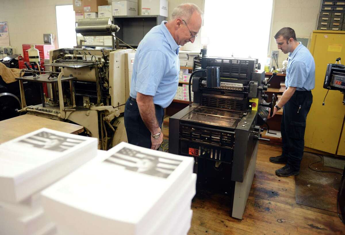 A file photo showing father and son Frank and Andrew Halpin working together at Ever Ready Press March 26, 2014, in Ansonia, Conn.