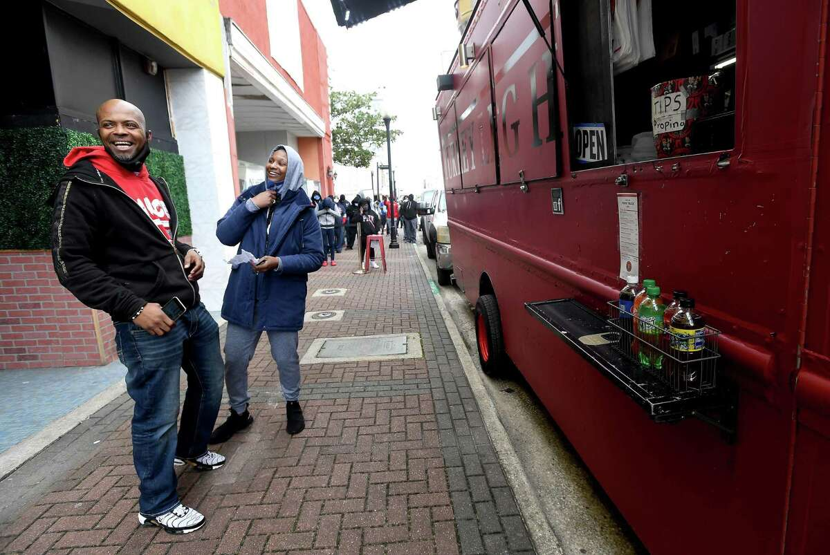 Lana Scott jokes with Al Henry, owner of Plush Lounge & Grill, as she finally makes her way to place an order after waiting two hours in a line that stretched down Orleans Street and onto Fannin in downtown Beaumont Friday for the weekend-long opening of Turkey Leg Hut's food truck. Henry was behind getting the food truck to Beaumont for its first stop in the area. He frequently gets to Houston for his favorite item, the shrimp alfredo turkey leg, but knows not everyone can make the trip,