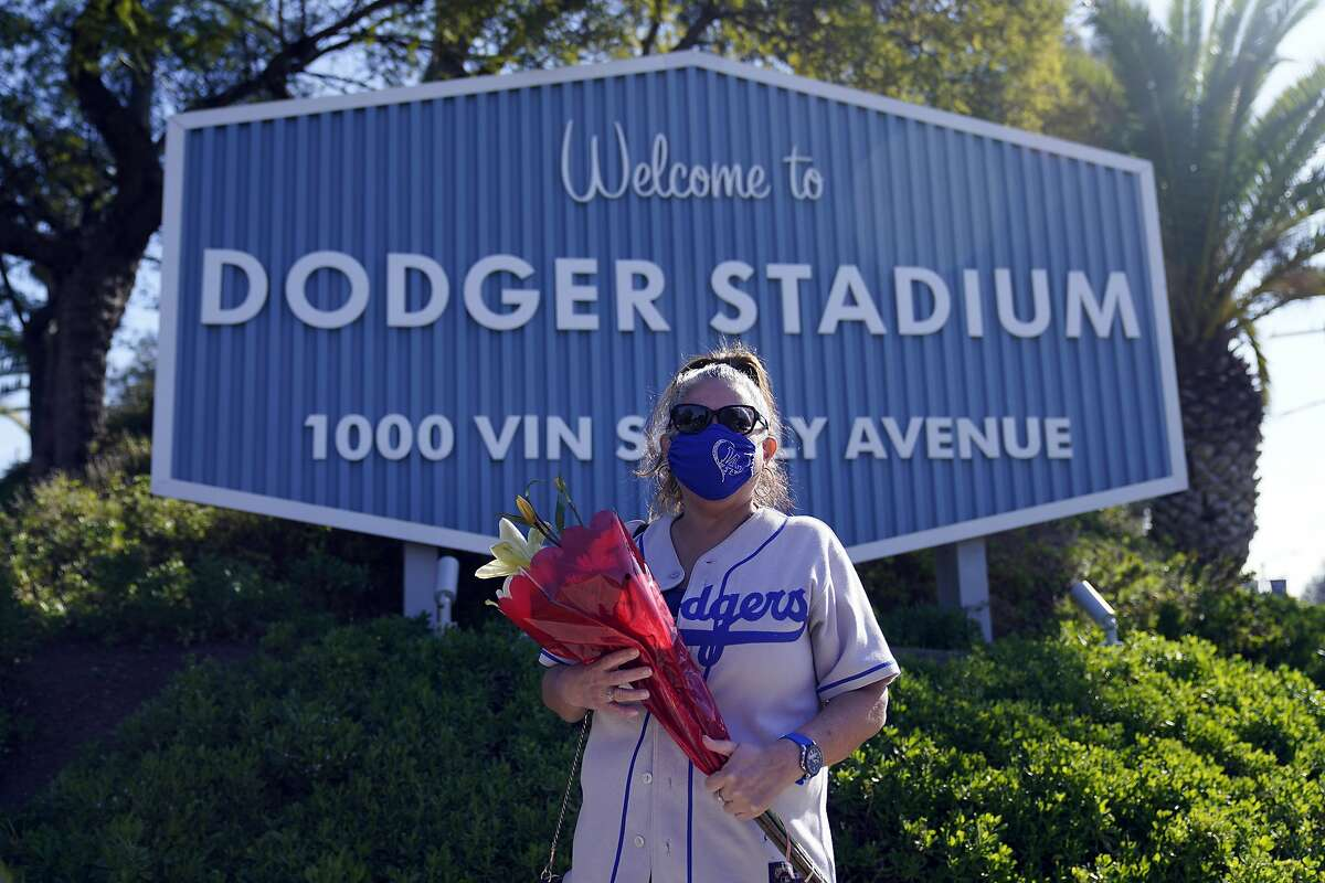 Dodgers fan Michelle Santisteban carries flowers to Dodger Stadium on Friday to honor the memory of Lasorda, who guided Los Angeles to two World Series titles.