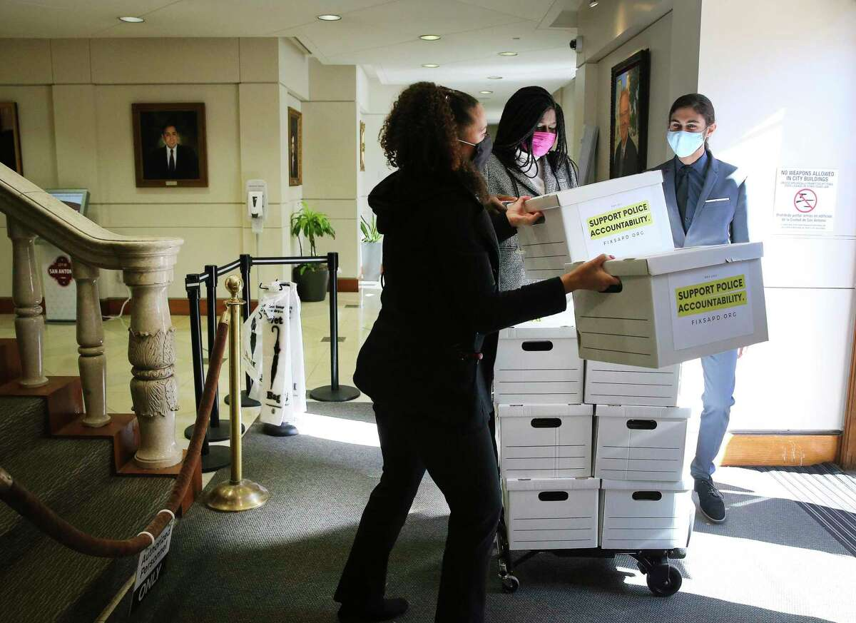 From left to right, Ananda Tomas, deputy director of Fix SAPD, Ojiyoma Martin, co-founder of Fix SAPD, and James Dykman, a board member, bring six boxes of roughly 20,000 signatures to the City Clerk's Office in an effort to repeal local implementation of Chapter 174.