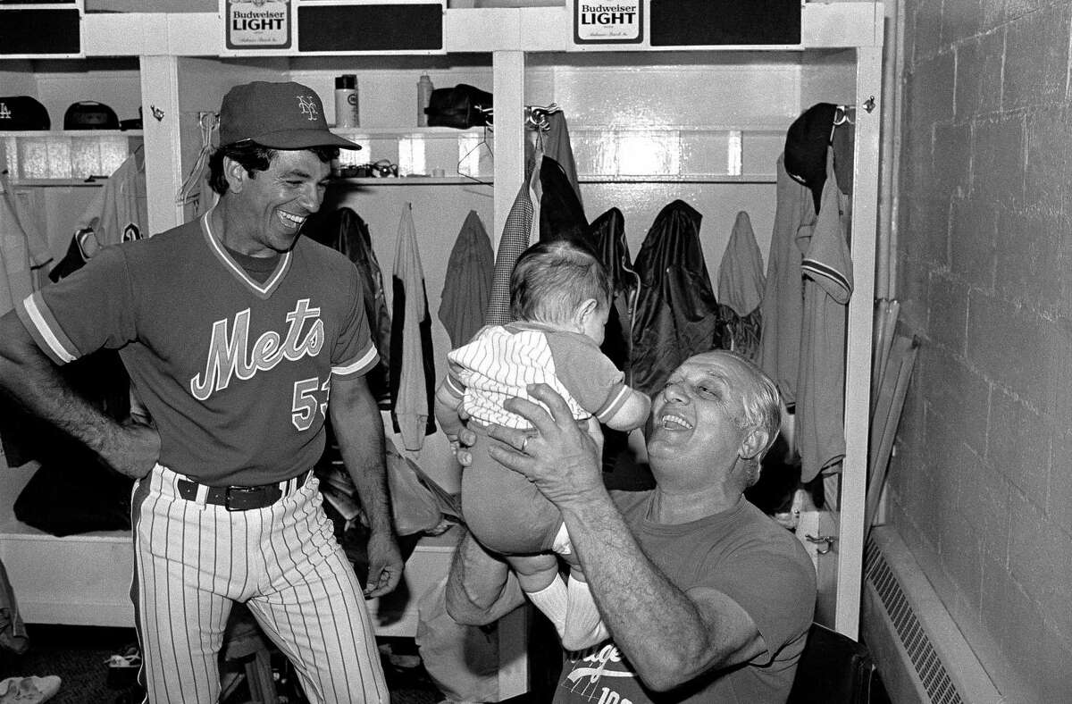 Dodgers manager Tom Lasorda lifts up Bobby Valentine, Jr., the four month old son of Mets coach Bobby Valentine, left, in the clubhouse at Shea Stadium in 1983.