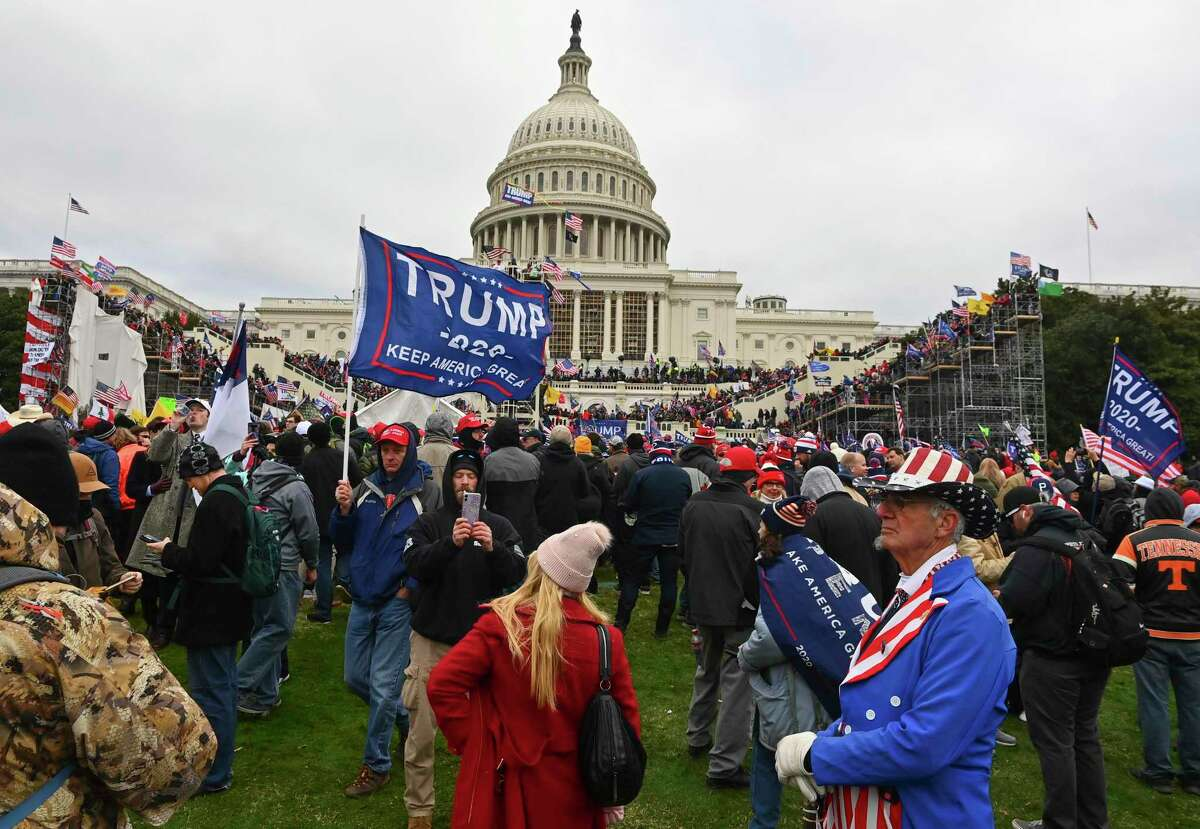 Protesters take over the Inaugural stage during a protest calling for legislators to overturn the election results in President Donald Trump's favor at the U.S. Capitol on Jan. 6, 2021, in Washington, D.C.