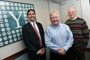 From left, Vlad Coric, CEO of Biohaven Pharmaceuticals, John Houston, president and CEO of Arvinas, and Jon Soderstrom, managing director of the Yale University Office of Cooperative Research, are photographed at the Office of Cooperative Research in New Haven on December 19, 2019. At left is a poster with companies that have been spun out of the Office of Cooperative Research.