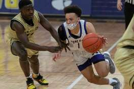Midland High's D'Cambrion White beats the press up court as he is held by Abilene High's Sami Kanayo 01/08/2021 at the Midland High gym. Tim Fischer/Reporter-Telegram