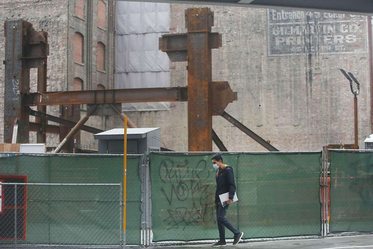 A pedestrian walks past the constrction site at 50 First Street on Friday, January 8, 2020 in San Francisco, Calif.
