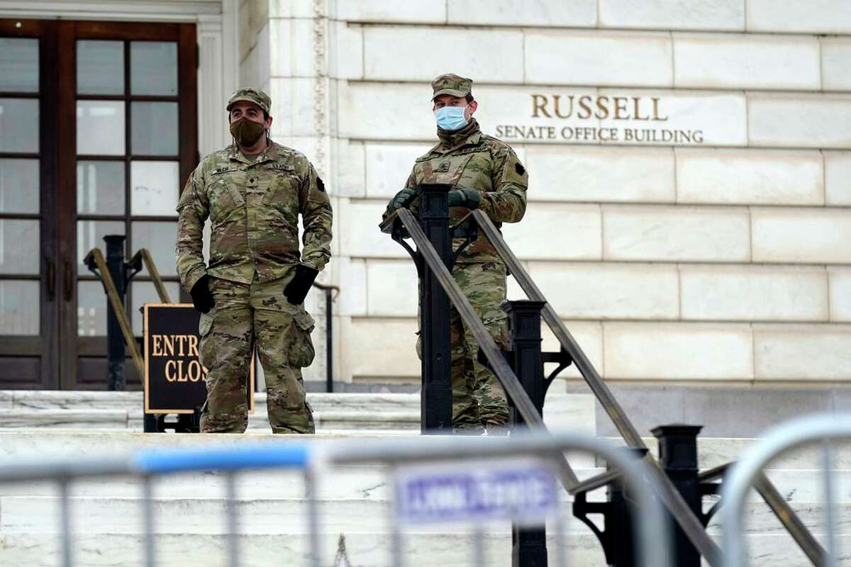 Members of the military stand guard outside Russell Senate Office Building on Capitol Hill in Washington, Friday, Jan. 8, 2021, in response to supporters of President Donald Trump who stormed the U.S. Capitol earlier in the week.