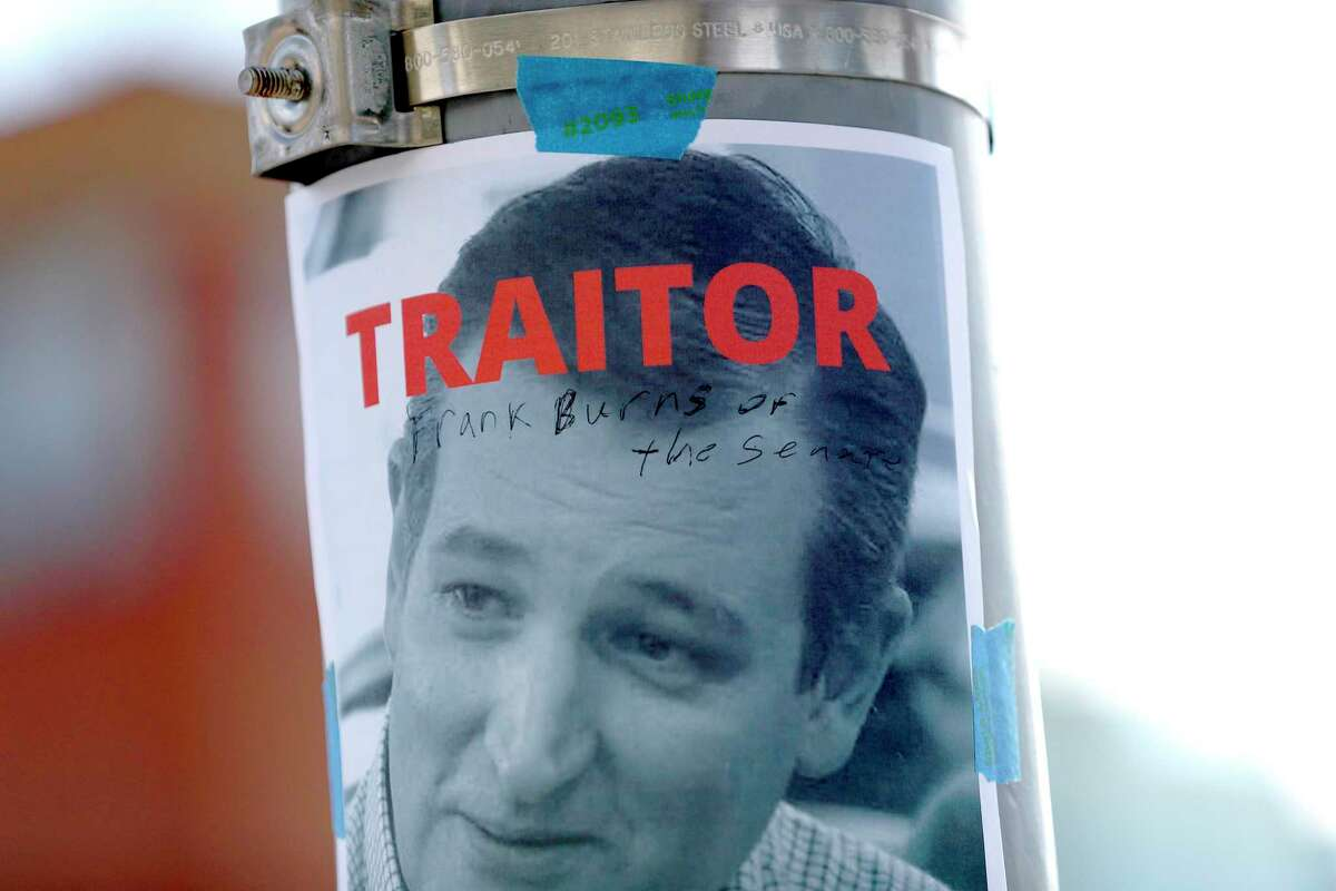 A protester writes on a photo of Senator Ted Cruz as he joined other Houston activists for a demonstration at the Leland Federal Building, in Houston, Thursday, Jan. 7, 2021, against the Trump supporters' disruption of Congress yesterday. The demonstration was organized by the Houston Socialist Movement, Houston United Front against Fascism, and People's New Black Panther Party.