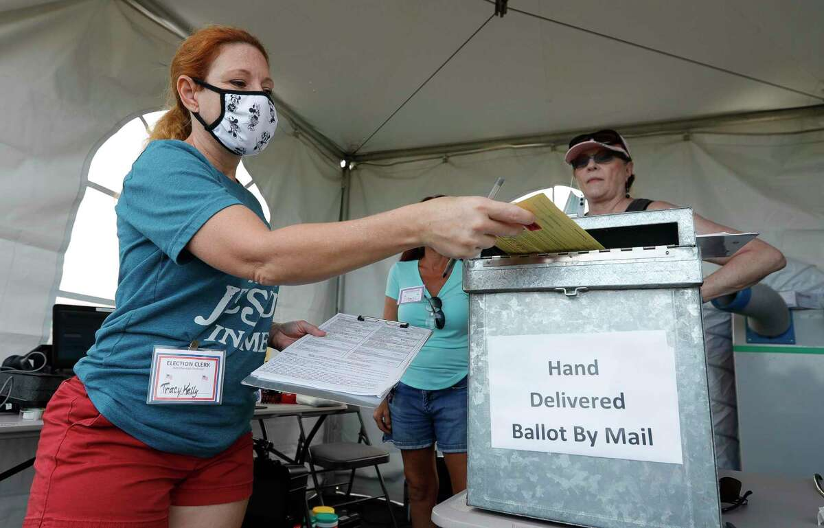 Election Clerk Tracy Kelly shows a resident as she securely submits his mail-in ballot, Thursday, Oct. 15, 2020, in Conroe. Texas counties may collect mail-in ballots at one location, Texas courts have ruled.