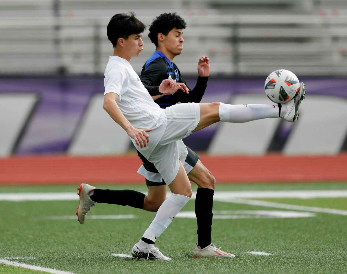 Oak Ridge's Edgar Chavez (12) kicks the ball away from New Caney's Javy Lopez (16) in the first period of a match during the Wildkat Showcase soccer tournament at Berton A. Yates Stadium, Friday, Jan. 8, 2021, in Willis.