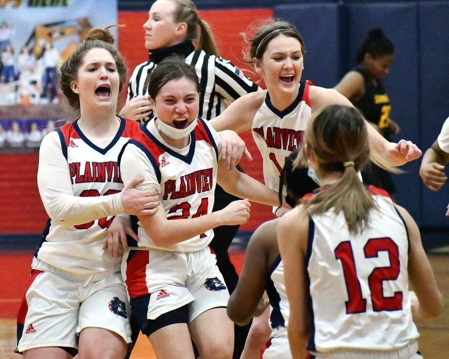 Plainview players, from left, Kylie Bennett, Janessa Pauda-Fulton and Katy Long rush to join their teammates to celebrate their 71-70 win over second-ranked Amarillo in a District 3-5A girls basketball game on Friday in the Dog House. Photo: Nathan Giese/Planview Herald