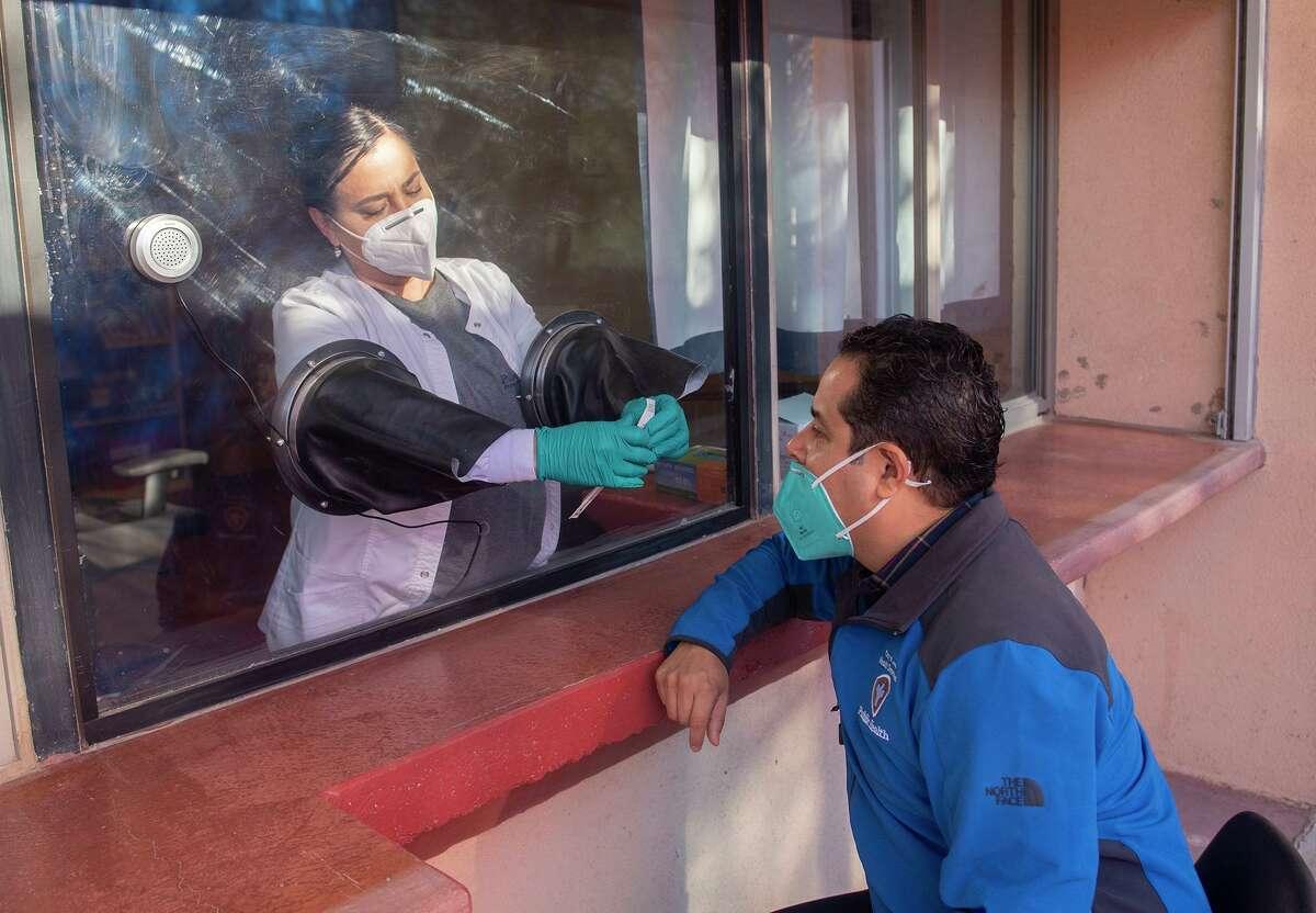 La asistente médica Eloisa Rodríguez y el jefe de servicios preventivos de salud, el Dr. Luis Cerda, demuestran las instalaciones del proceso de prueba COVID-19, el jueves 7 de enero de 2021, durante la apertura suave de la Clínica Sur del Departamento de Salud de la Ciudad de Laredo dentro de la Biblioteca Santa Rita Express. .