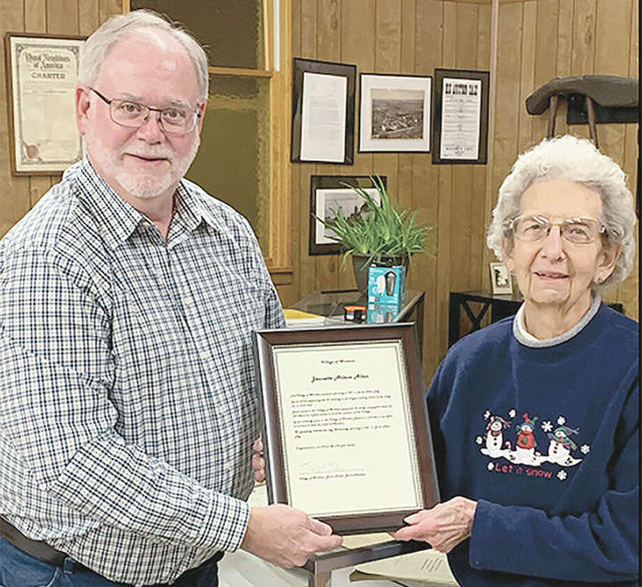 Janet Allen (right) of Woodson is recognized by village President Bruce Milner during a board meeting. Wednesday was proclaimed Janet Allen Day in the village.
