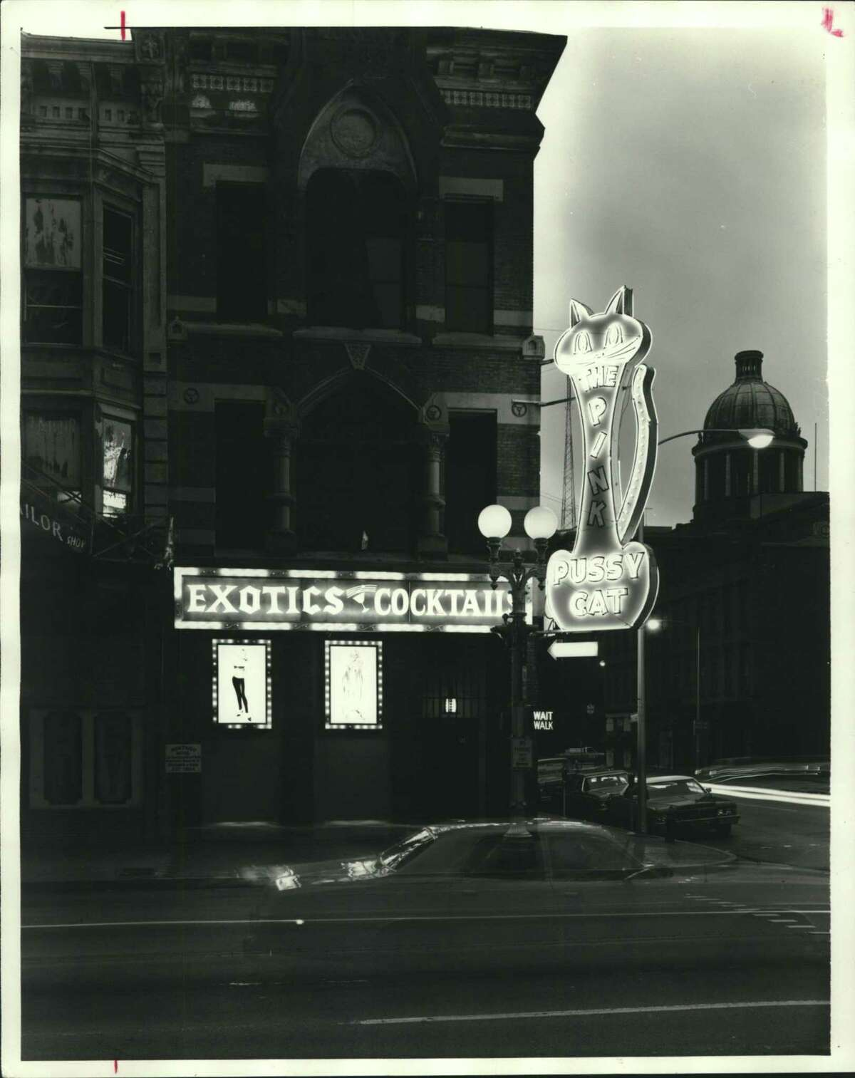 This iconic bright pink neon sign marks the Pink Pussy Cat lounge in Houston at the corner of Main and Congress avenues in 1979. The building was demolished in 1983.