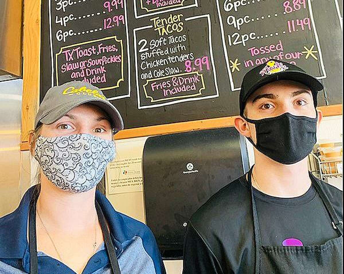 Lindsey Bowers and Matt Myers mask up prepared to take orders from a line of customers at Mack's Tenders in Cypress after the business was saved by a donation from Barstool Sports.