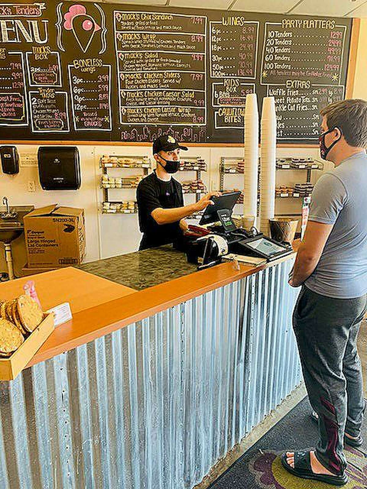 Matt Myers takes an order at Mack's Tenders with his mask on takes an order from a masked customer. The business got a boost from Barstool Sports with a donation that will help them monthly through the pandemic.