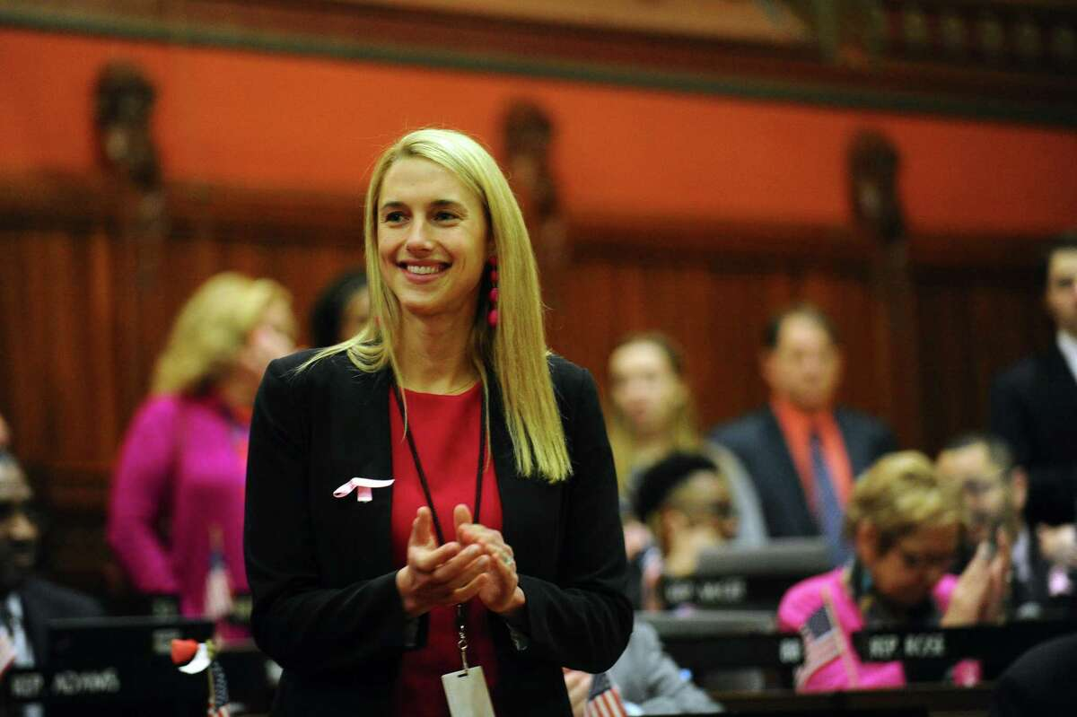 Rep. Caroline Simmons, D-Stamford, stands and applauds during the Connecticut State Legislature's first session of the year inside the House chamber of the State Capitol in Hartford, Conn. on Wednesday, Feb. 7, 2018.