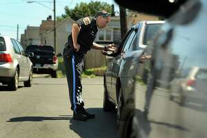 File photo. Danbury police Officer Ricard DeJesus stops a car on West Street after observing the driver using a mobile device.