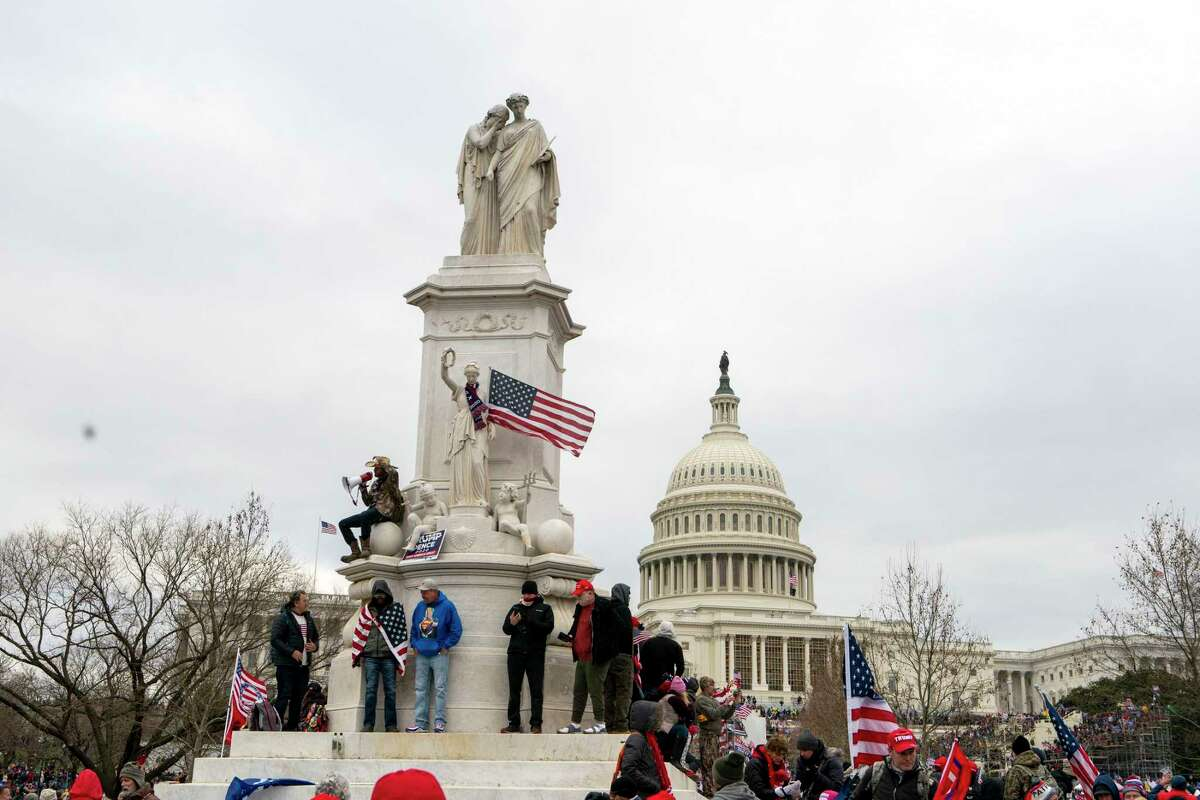Supporters of President Donald Trump climb the Peace Monument, also known as the Naval Monument or Civil War Sailors Monument, during a rally at the U.S. Capitol on Wednesday, Jan. 6, 2021, in Washington. (AP Photo/Jose Luis Magana)