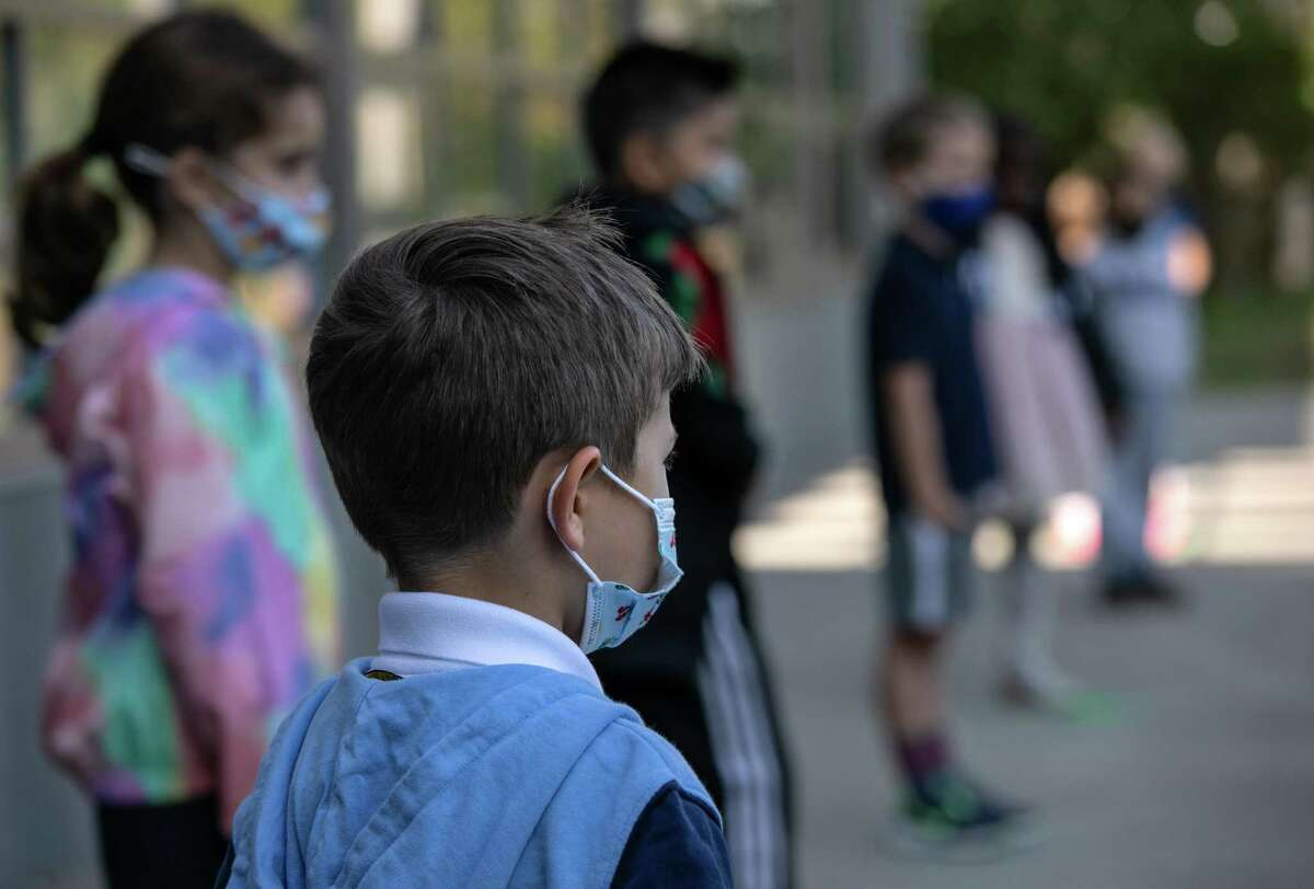 Masked school children wait to have their portraits taken during picture day at Rogers International School on September 23, 2020 in Stamford, Connecticut.