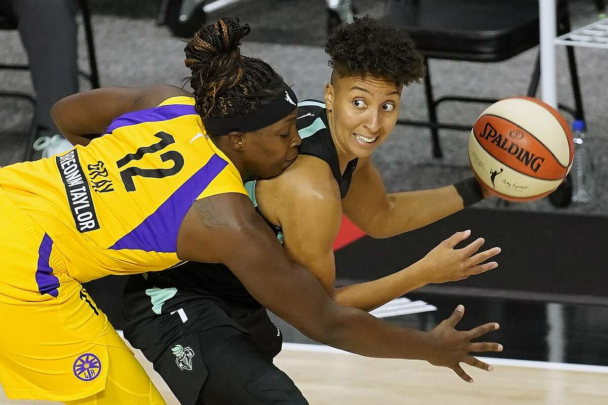 Los Angeles Sparks guard Chelsea Gray (12) ties up New York Liberty guard Layshia Clarendon (7) during the first half of a WNBA basketball game Tuesday, Sept. 8, 2020, in Bradenton, Fla. (AP Photo/Chris O'Meara)