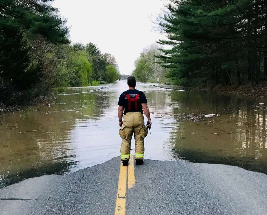 Firefighter Aaron Boxey looks out onto a washed outSaginaw Road, east of the Jerome Township Fire Station after the dam failures in May 2020. (Facebook photo/Jerome Township Fire Department) Photo: Photo Provided