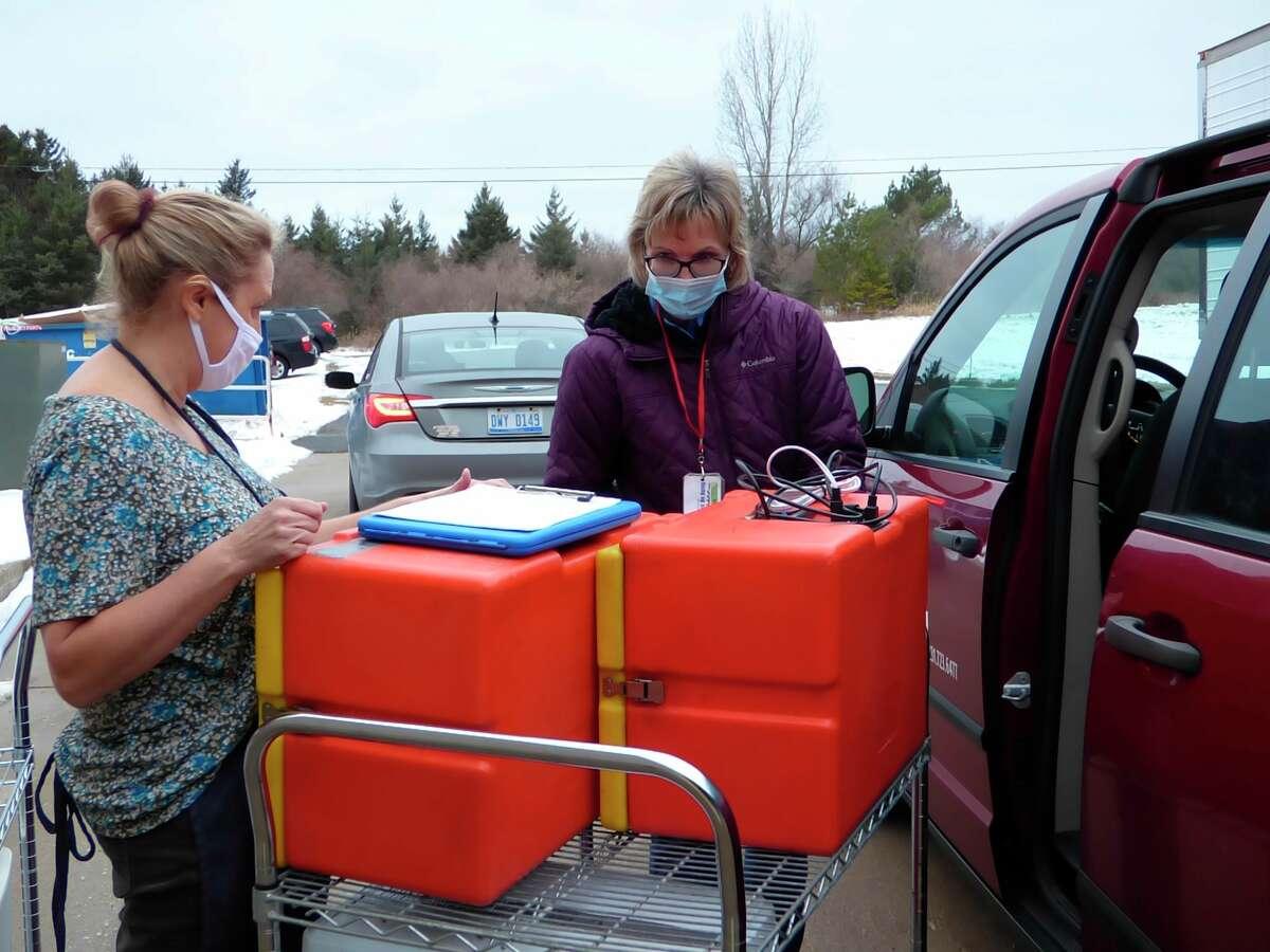 Keri Carlson (left) and Nancy Fortin prep meals for homebound seniors. (Scott Fraley/News Advocate)