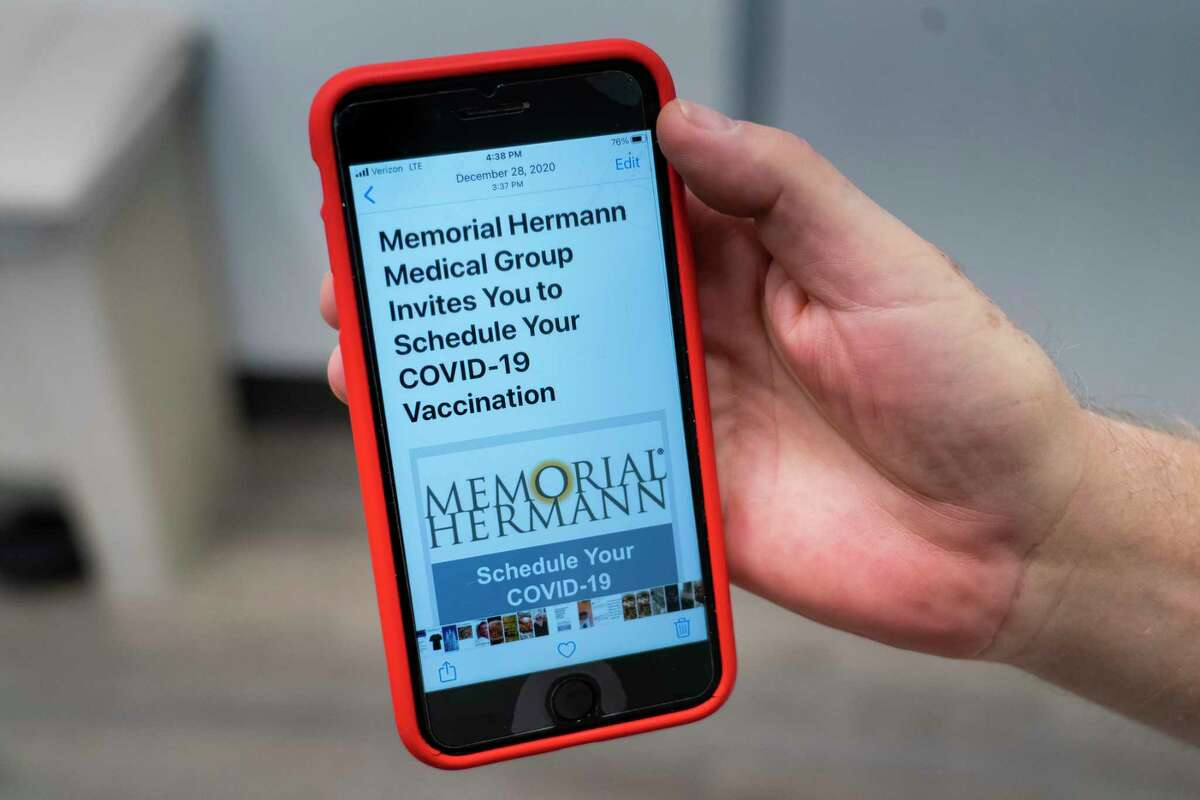 Bill Braido holds a picture of the email he received asking him to schedule his first does of the COVID-19 vaccine after receiving the shot during an appointment at a Memorial Hermann Medical Group office on West Holcombe Boulevard, Friday, Jan. 8, 2021, in Houston. Braido, 67, is currently receiving chemotherapy treatments at Memorial Hermann for stage 1 bladder cancer, and received the email during the last week of December asking him to schedule an appointment to receive the vaccine.