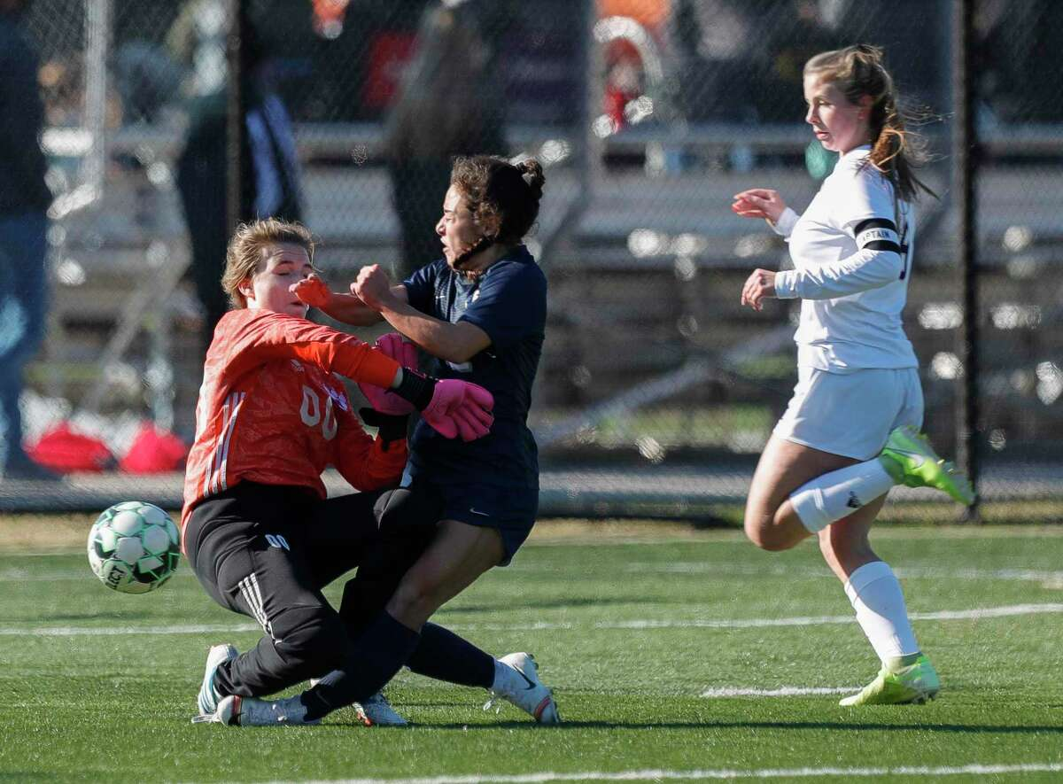 College Park's Mia Summers (22) collides with Montgomery goalie Kailea Oliver (00) in the first period of a match during the Lady Highlander Invitational, Saturday, Jan. 9, 2021, in The Woodlands.